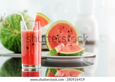 Glass of fresh watermelon juice on table in kitchen. Ripe watermelons and slices in background. Healthy eco sweet food rich in vitamins. Popular product of organic farming. - stock photo