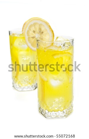 Glass of freshly made cold lemon beverage with pieces of the fruit - stock photo
