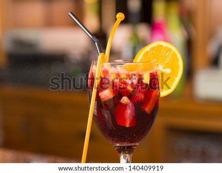 Glass of freshly prepared sangria against a bar background - stock photo