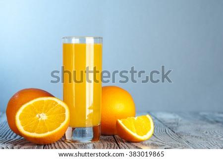 Glass of freshly squeezed orange juice, ripe oranges on wooden table - stock photo