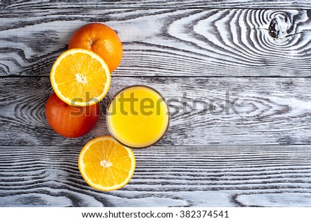 Glass of freshly squeezed orange juice, ripe oranges on wooden table. Overhead view. - stock photo