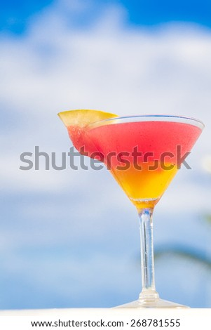 glass of fruit cocktail  on table near the beach - stock photo