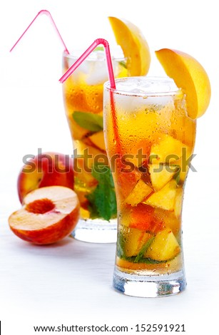 Glass of fruit iced peach Mojito cocktail with mint