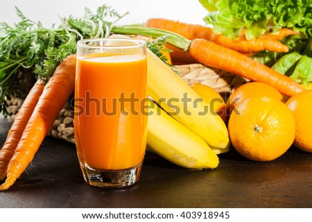 Glass of fruit juice with orange, carrots and banana on a table - stock photo
