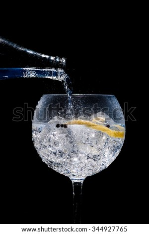 glass of gin and tonic on black background - stock photo