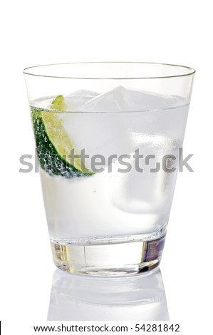 Glass of gin and tonic with ice cubes and lime wedge - stock photo