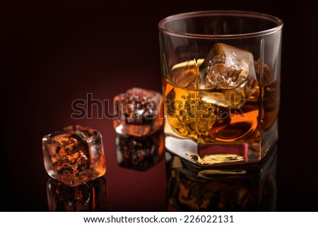 Glass of gold color luxury whiskey and ice - stock photo