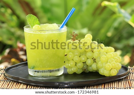 Glass of Grape Juice smoothie on the table - stock photo