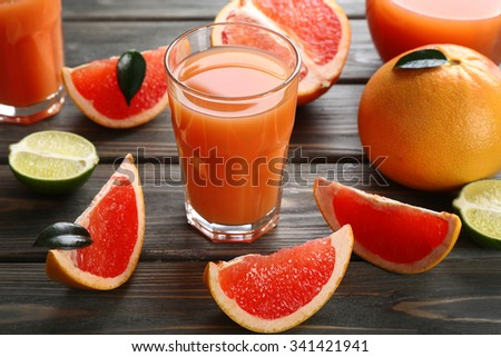 Glass of grapefruit juice and fresh fruits on wooden background
