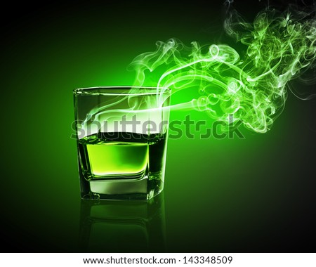 Glass of green absinth with fume going out - stock photo