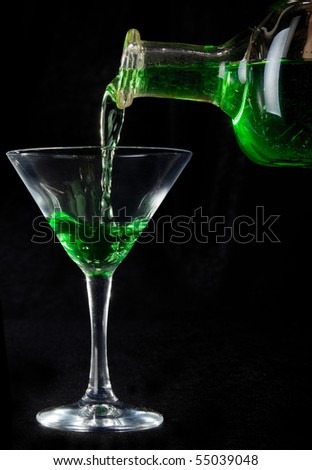 glass of green cocktails and bottle on black - stock photo