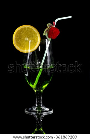 Glass of green drink with bendie and orange slice on black mirror background - stock photo