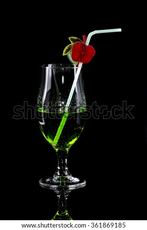 Glass of green drink with bendie on black mirror background - stock photo