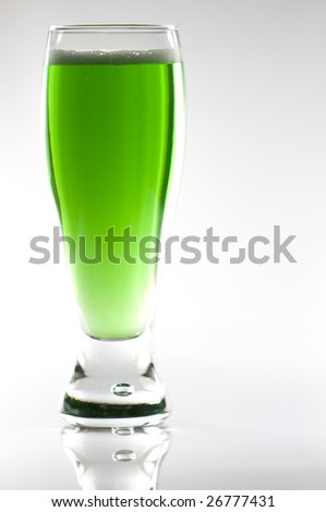 Glass of green irish beer for St-Patrick's day. On shiny white surface and white background.