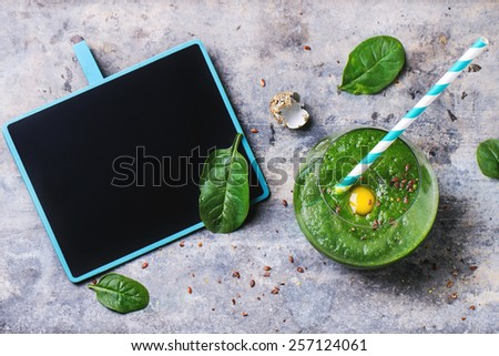 Glass of green smoothie with quail egg's yolk, served with blank black chalkboard, cocktail tube and baby spinach leaves over tin surface. Top view. - stock photo