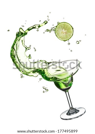 glass of green splashing cocktail with lime