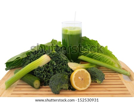 Glass of green vegetable juice with fresh vegetables on a cutting board, over white - stock photo