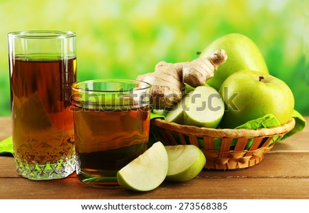 Glass of healthy fresh juice of apples and ginger on wooden background - stock photo