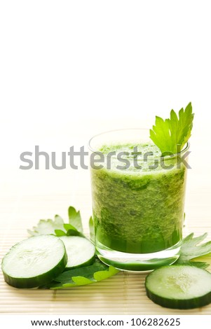 Glass of healthy green cucumber smoothie decorated with celery leaves - stock photo