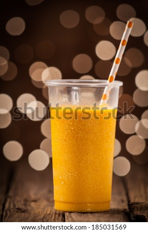 Glass of healthy refreshing cold orange mango smoothie with a straw on a wooden counter with a festive sparkling bokeh of party lights - stock photo