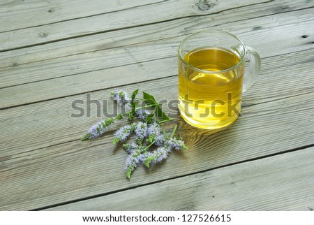 glass of herbal tea and peppermint blossoms on rustic wooden table background