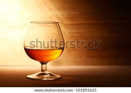 Glass of hot cognac over wooden surface - stock photo
