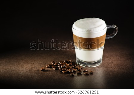 Glass of hot Latte macchiato coffee close up
