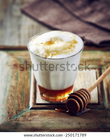 Glass of hot milk with honey - stock photo