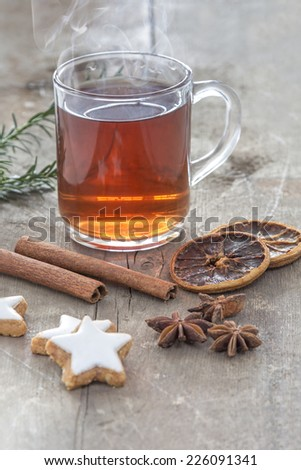 Glass of hot spiced wine with cinnamon oranges and star anise on rustic wooden table - stock photo