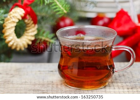 Glass of hot steaming tea among christmas decorations. Copy space - stock photo