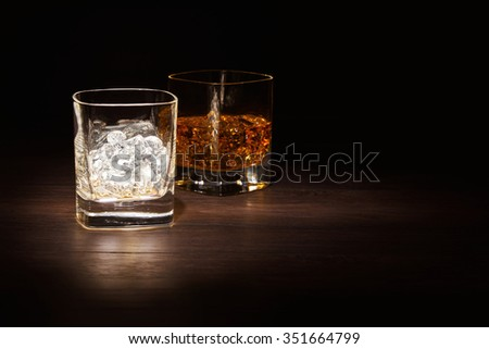 Glass of Ice and a Single Malt Whiskey in a glass on a wooden table top. - stock photo