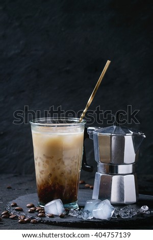 Glass of ice coffee with cream and milk, served with coffee beans, ice cubes and coffee pot on slate stone board over black textured background. - stock photo