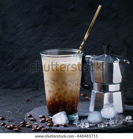 Glass of ice coffee with cream and milk, served with coffee beans, ice cubes and coffee pot on slate stone board over black textured background. Square image - stock photo