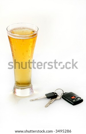 Glass of ice cold beer and car keys isolated on a white background.