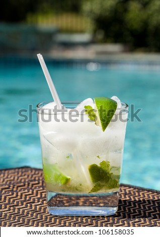Glass of ice cold majito in glass by side of swimming pool - stock photo