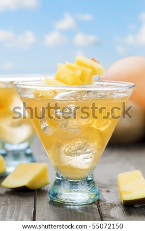 Glass of ice cold mango beverage on wooden table top and blue sky - stock photo