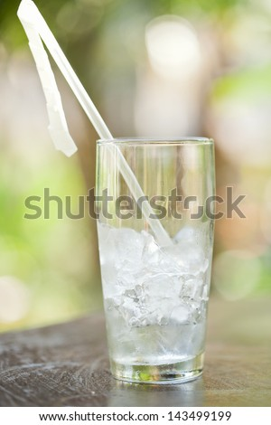 Glass of ice cubes with a straw - stock photo