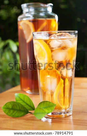 glass of ice tea with lemon and pitcher on a background - stock photo