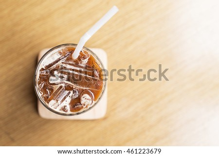 glass of iced coffee on wooden table background.