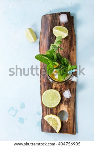 Glass of Iced green tea with lime, lemon, mint and ice cubes on wooden chopping board over light blue textured background. Flat lay. With copy space. Focus on mint - stock photo