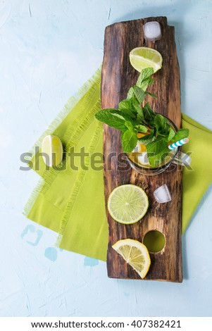 Glass of Iced green tea with lime, lemon, mint and ice cubes on wooden chopping board over light blue textured background with green textile napkin. Flat lay - stock photo