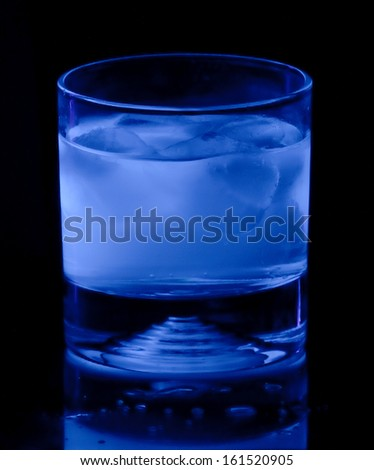 glass of iced tonic water glows blue under ultraviolet black light - stock photo