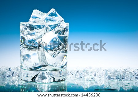 Glass of iced water in a pool of water and ice in blue