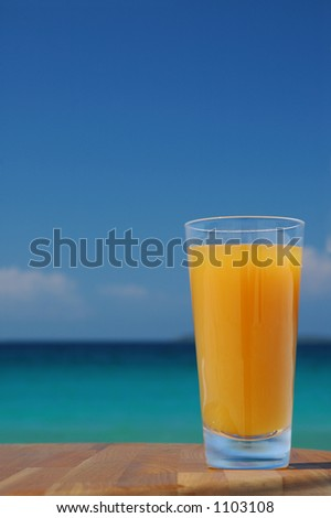 Glass of Juice Against Tropical Sea. - stock photo