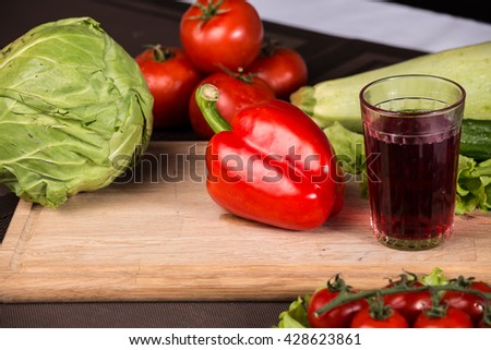 Glass of juice, red pepper and fresh vegetables - close up photo