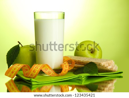 Glass of kefir, apples, crispbreads and measuring tape, on green background - stock photo