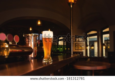 Glass of lager beer on bar of restaurant - stock photo