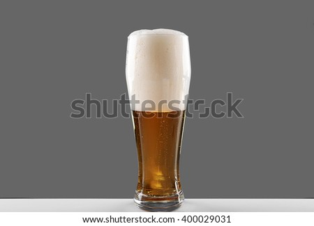 Glass of lager beer on grey background - stock photo