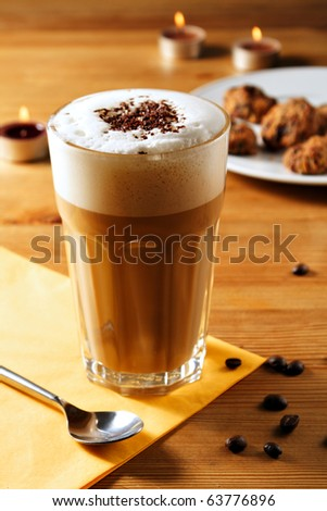 glass of Latte Macchiato with spoon, candles, napkin coffee beans and plate with cookies on a wooden table - stock photo