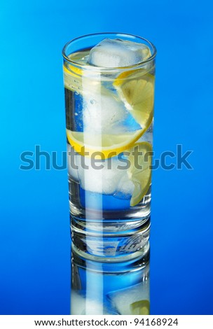 Glass of lemon ice water on blue background, studio photo
